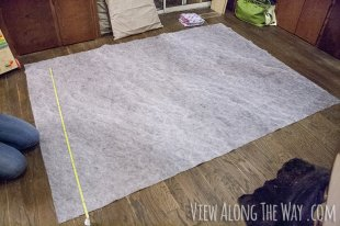 Lay out the rug underlay and the faux fur fabric and cut them to the same size. (In our case, 5×7 feet.)