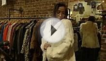 Girl Tries On Fur Coat In Vintage Clothing Store Stock